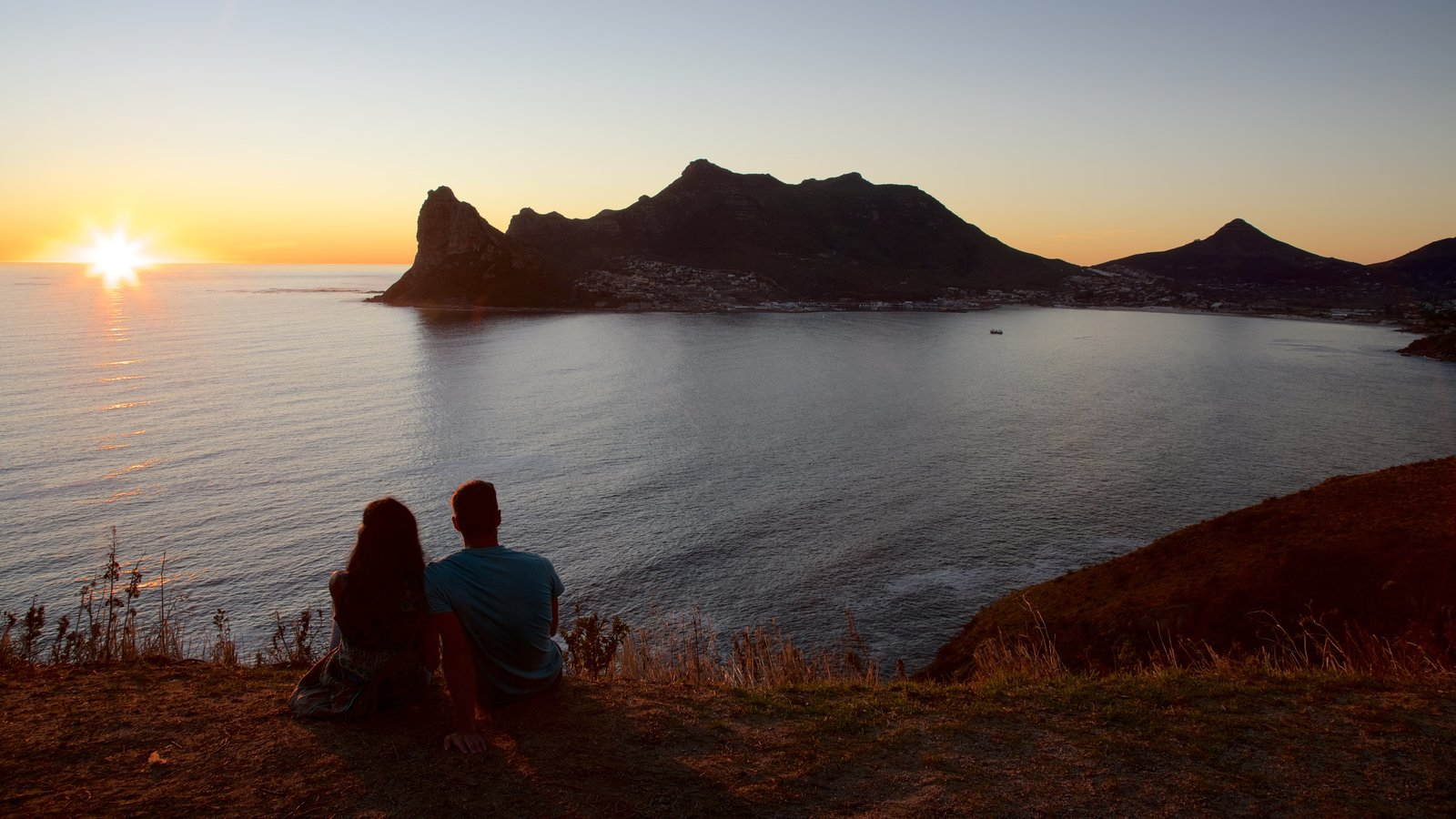 Chapmans Peak showing rugged coastline and a sunset as well as a couple