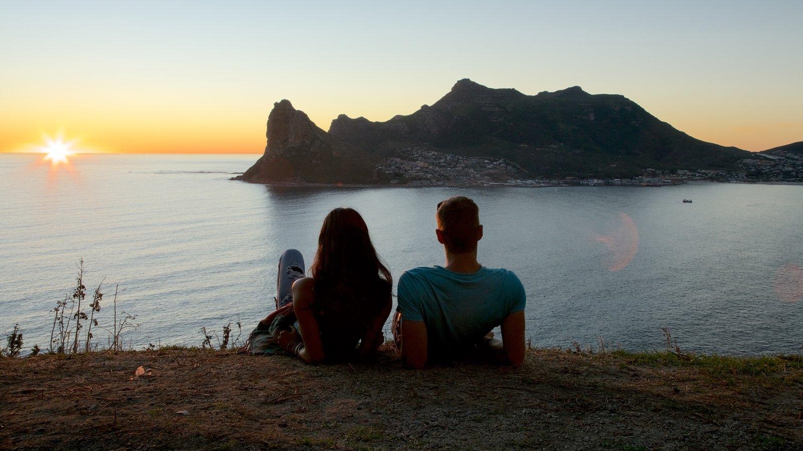 Chapmans Peak caracterizando um pôr do sol e litoral rochoso assim como um casal