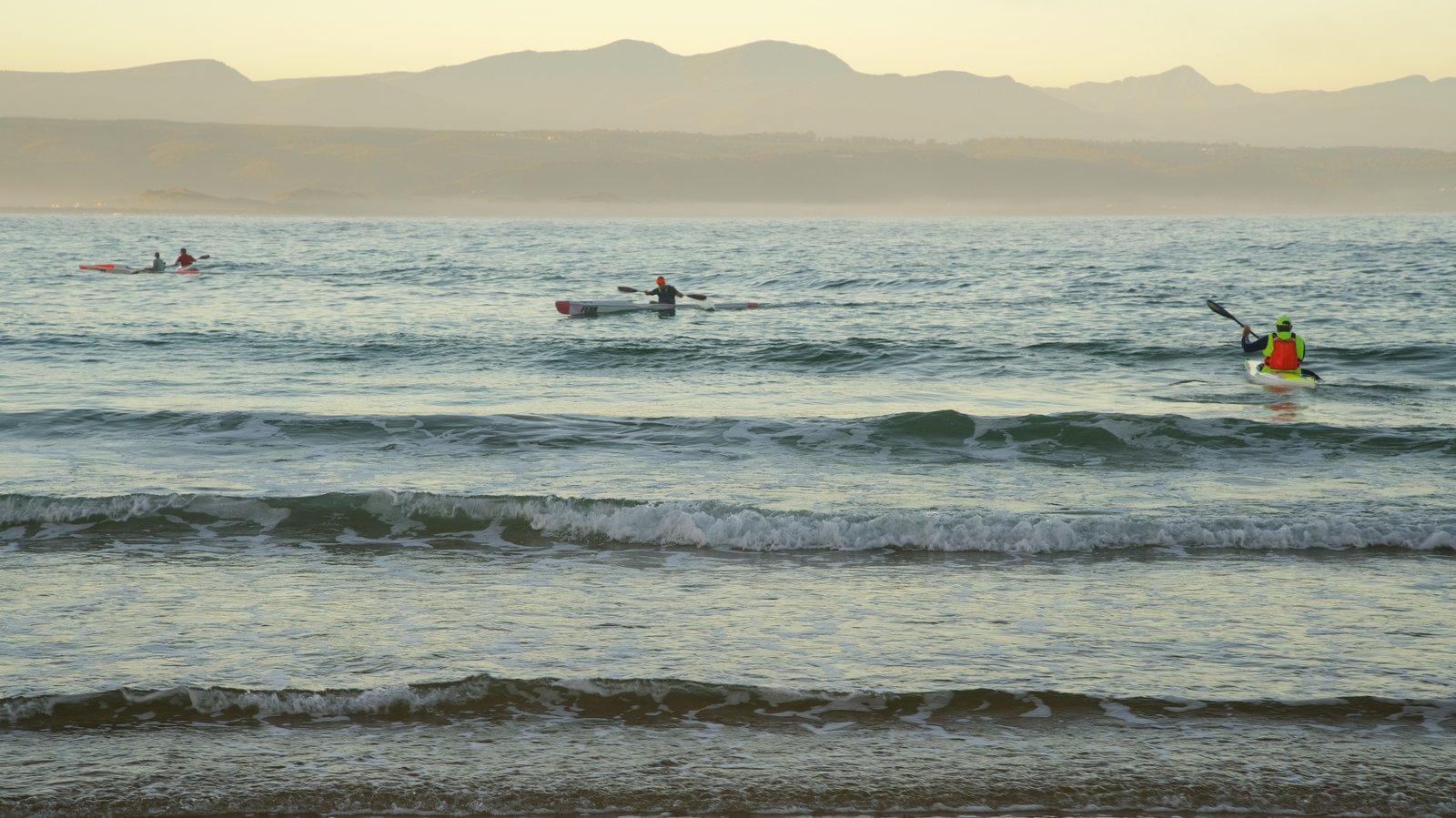 Praia da Baía Plettenberg mostrando uma praia e caiaque ou canoagem assim como um pequeno grupo de pessoas