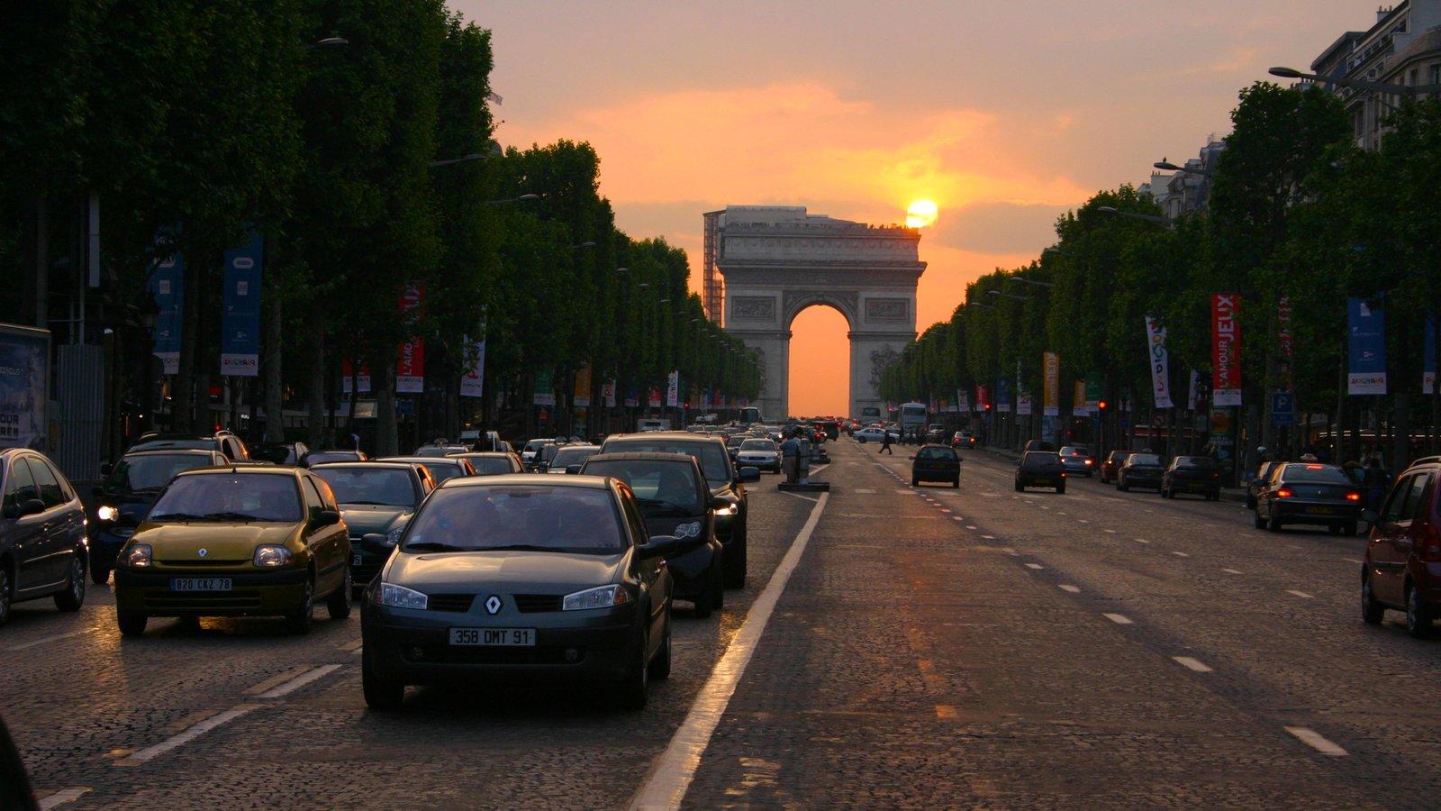 Arco do Triunfo mostrando um pôr do sol, cenas de rua e um monumento