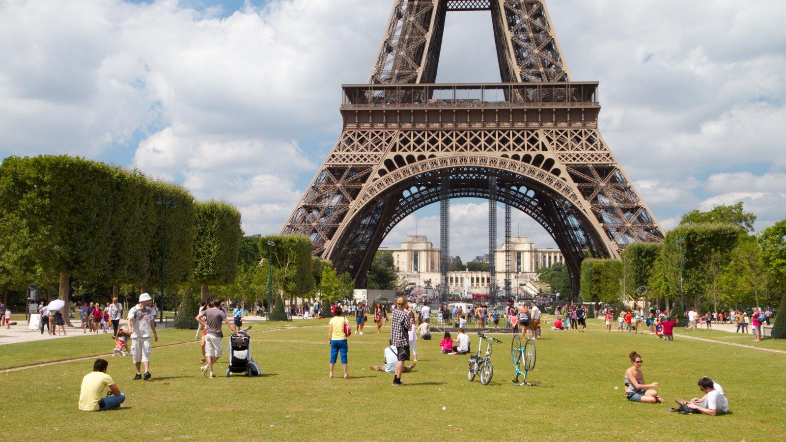 Torre Eiffel caracterizando uma cidade e um parque assim como um grande grupo de pessoas