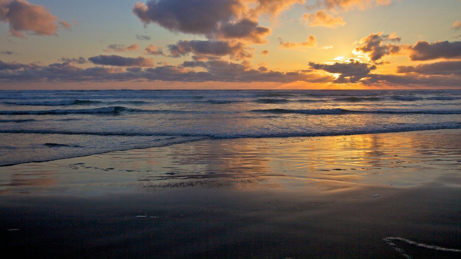 Cannon Beach ofreciendo una puesta de sol, una playa de arena y vistas de paisajes