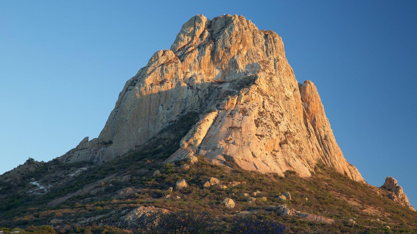 Pena de Bernal que inclui um pôr do sol e montanhas