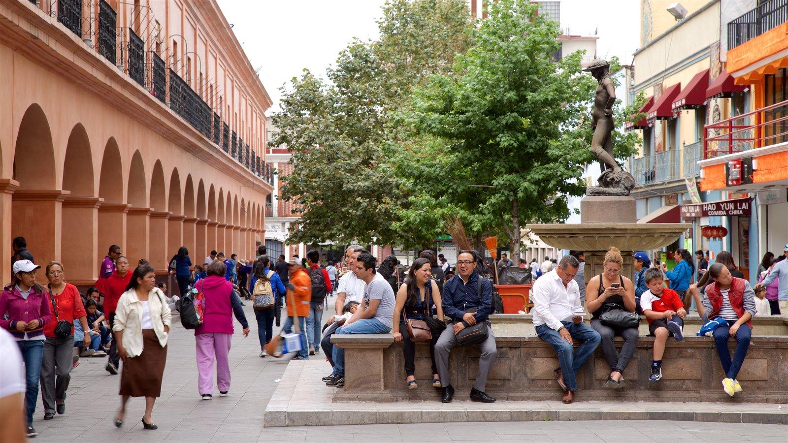 Toluca que incluye un parque o plaza y una fuente y también un pequeño grupo de personas