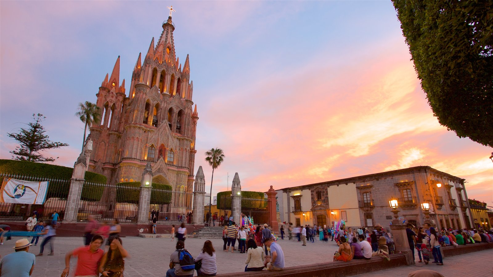 Igreja Paroquial de San Miguel Arcangel caracterizando uma praça ou plaza, um pôr do sol e arquitetura de patrimônio