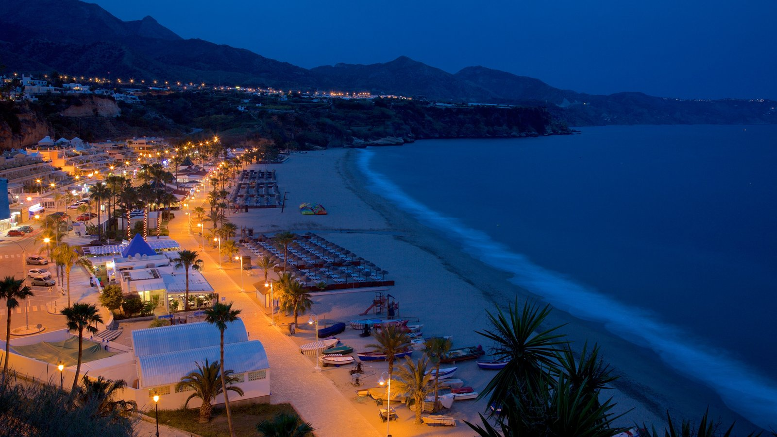 Burriana Beach featuring night scenes, a bay or harbor and a coastal town