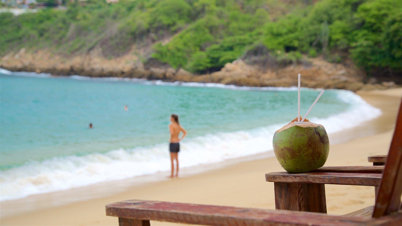 Playa de Carrizalillo mostrando una playa de arena y vistas generales de la costa y también una mujer