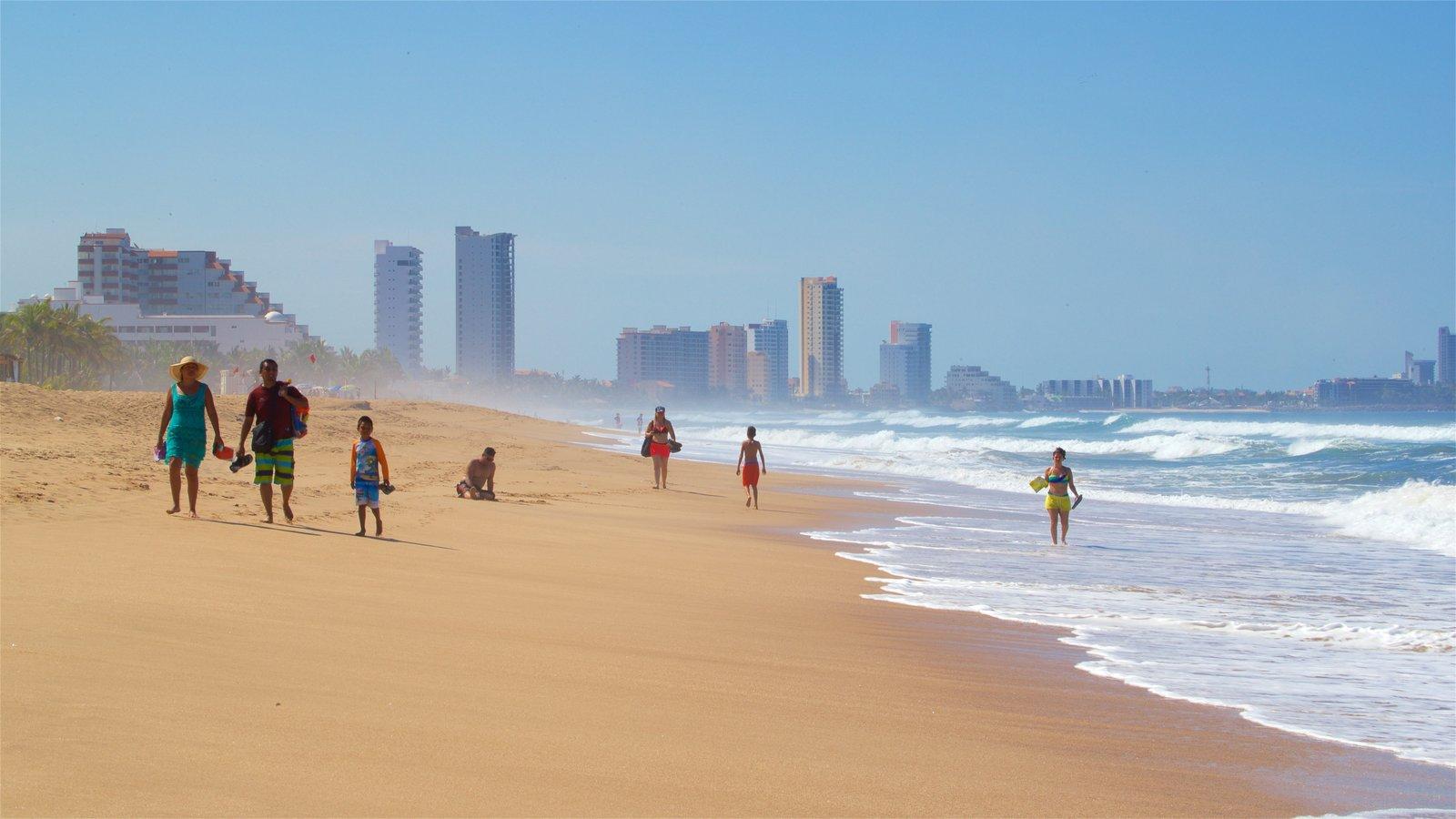 Personas caminando por la playa de Mazatlán