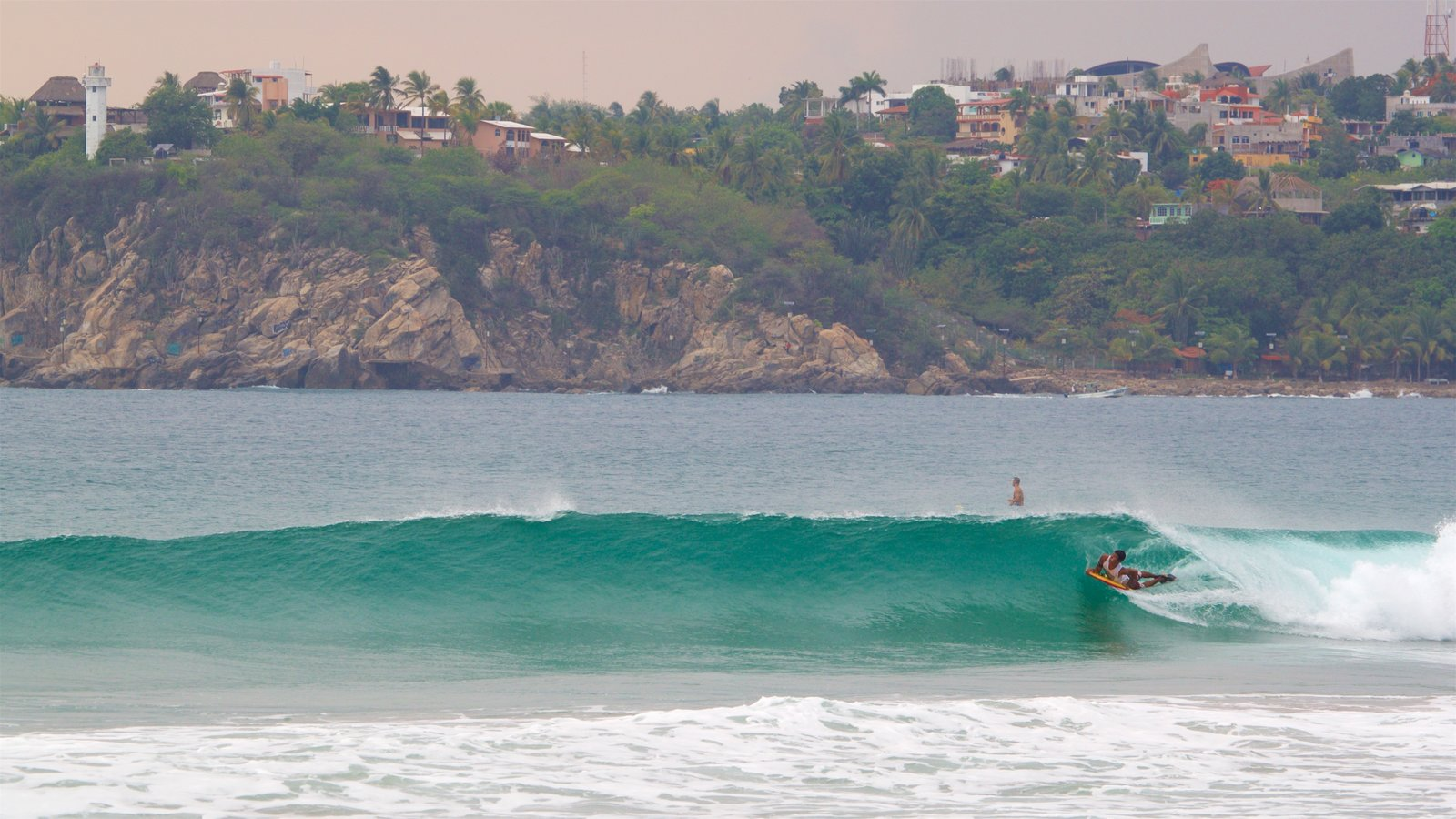 Zicatela Beach which includes waves, surfing and rocky coastline