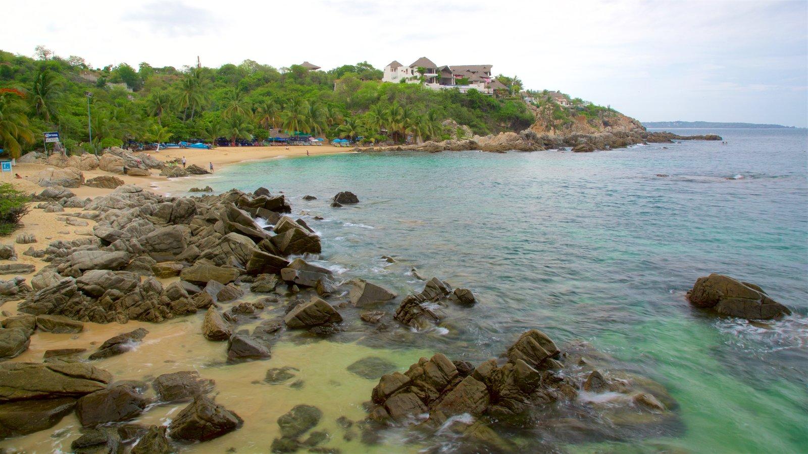 Playa Puerto Angelito que incluye una playa, costa escarpada y vistas generales de la costa