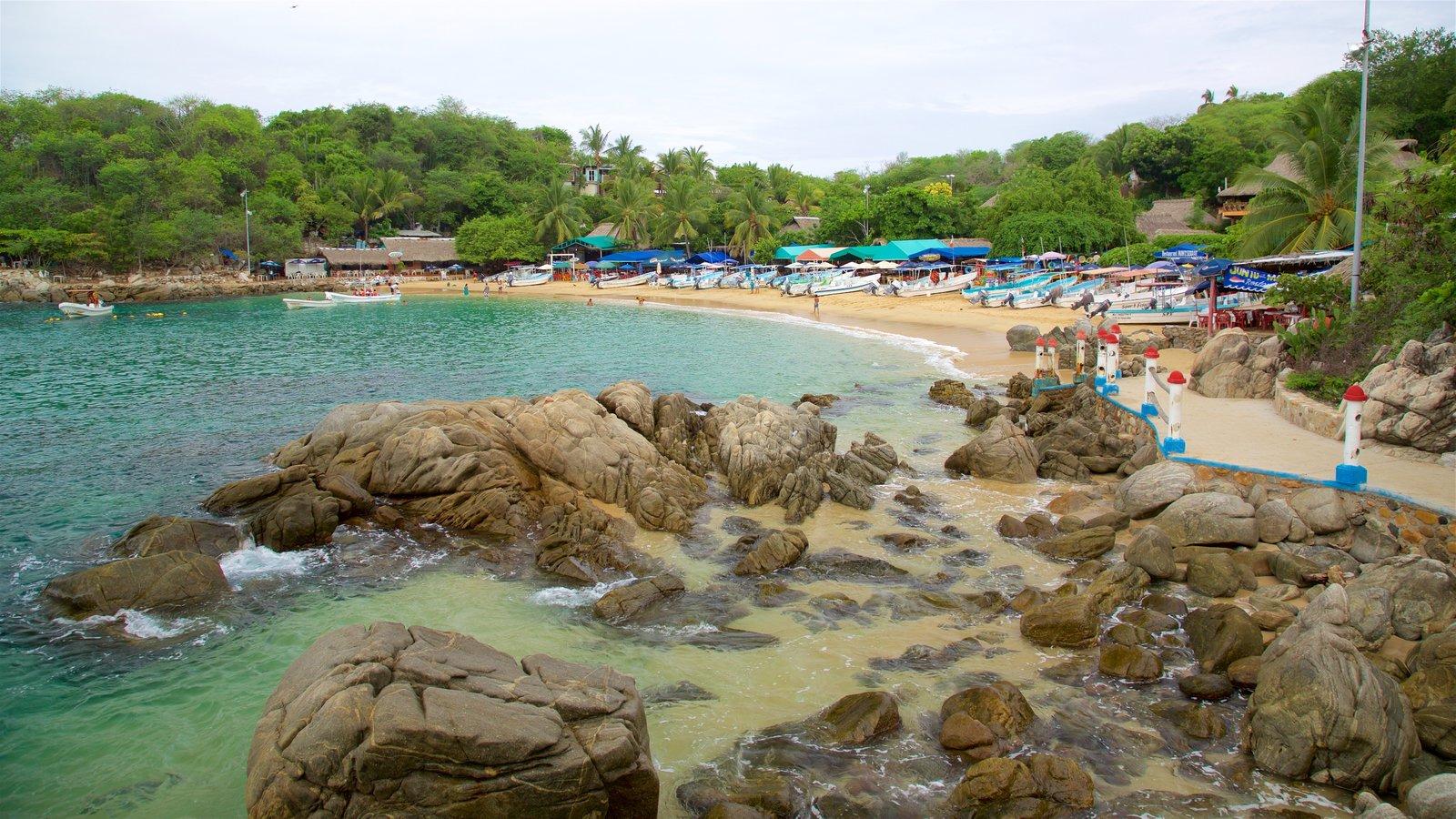 Playa Puerto Angelito mostrando escenas tropicales, una playa y costa escarpada