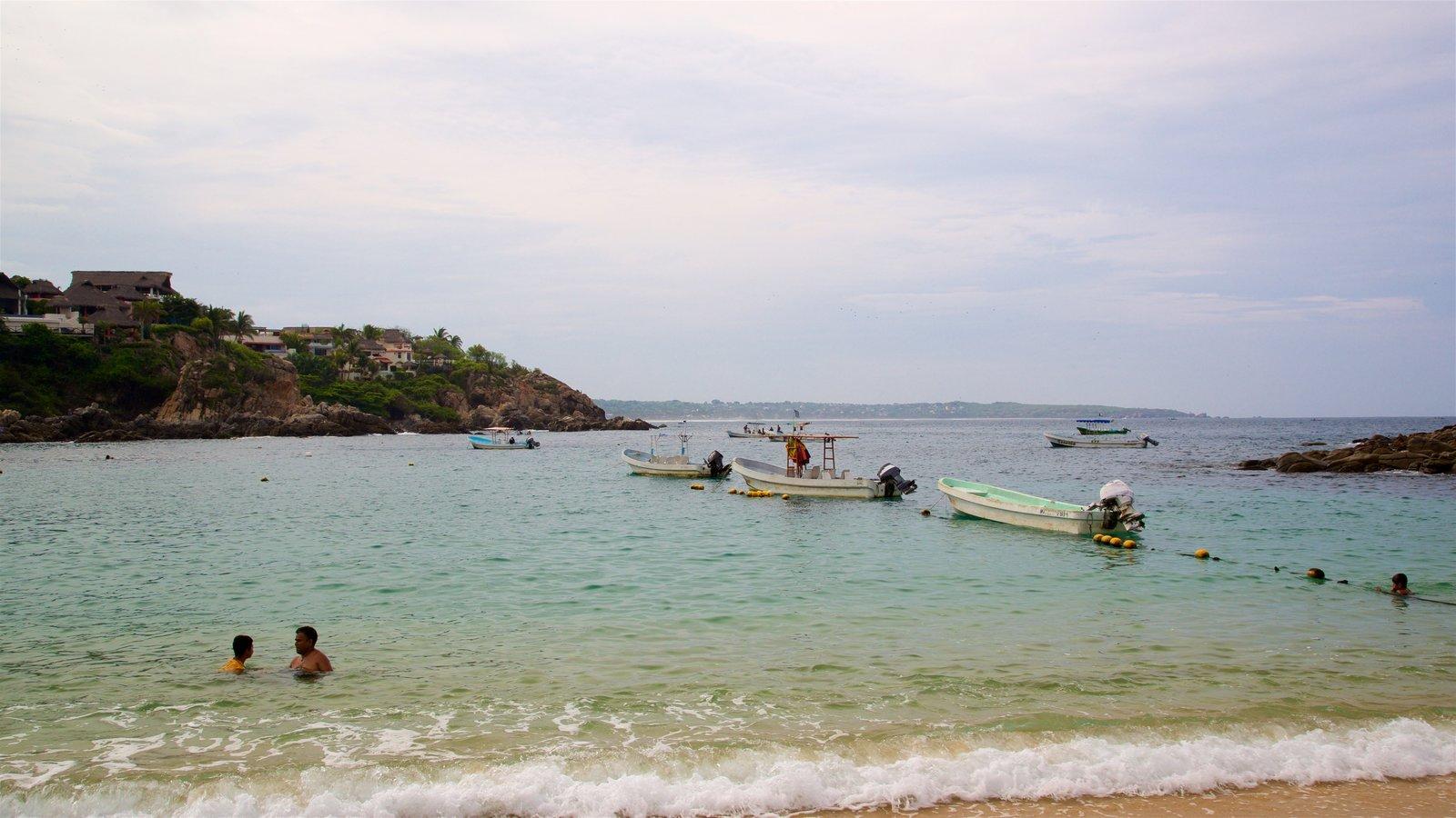 Playa Puerto Angelito ofreciendo natación, vistas generales de la costa y paseos en lancha
