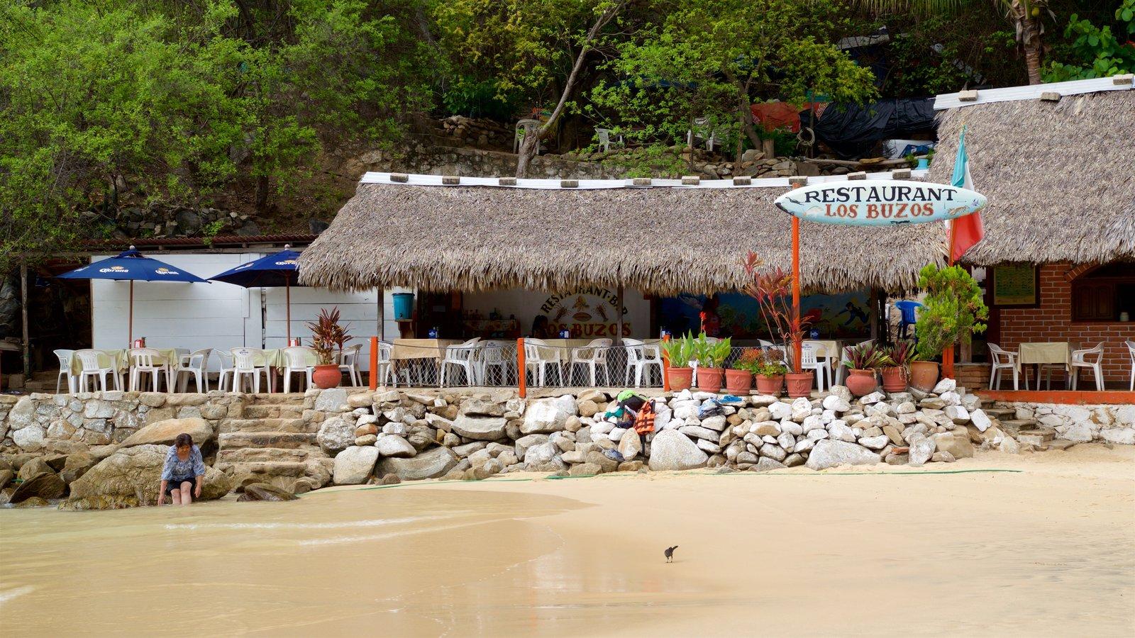 Playa Puerto Angelito que incluye una playa de arena, costa escarpada y escenas tropicales
