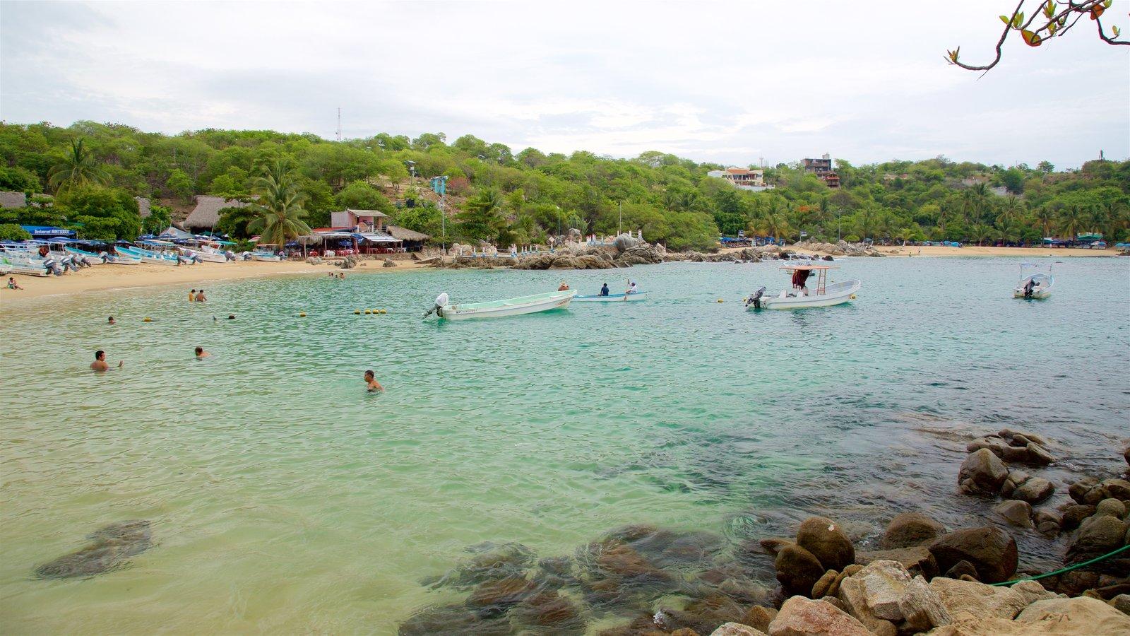 Playa Puerto Angelito que incluye vistas generales de la costa, paseos en lancha y una playa de arena