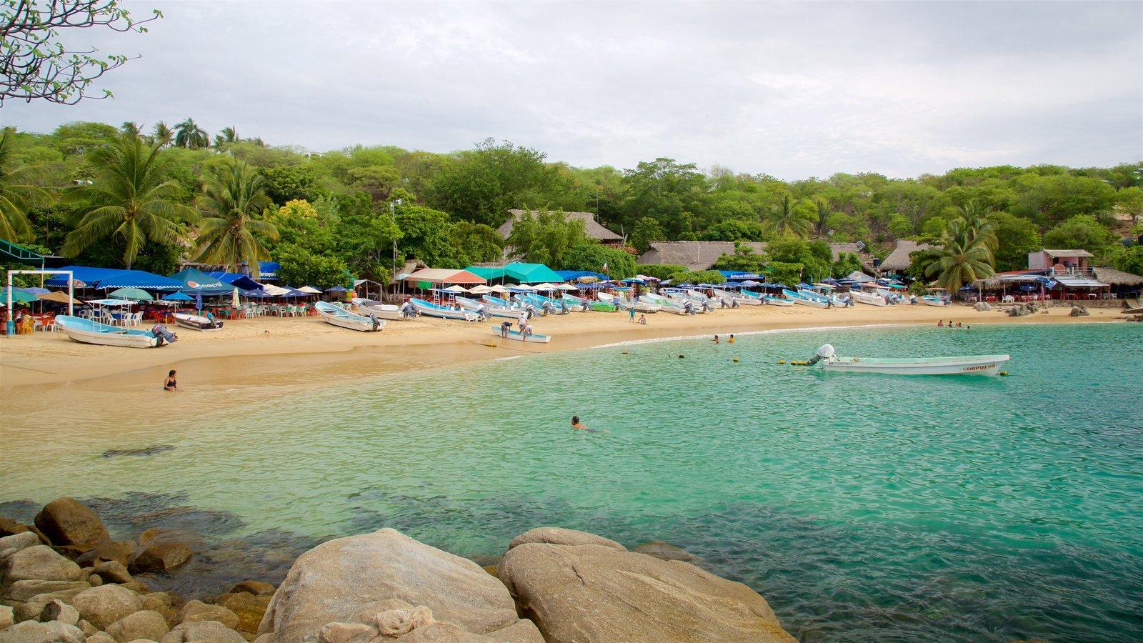 Playa Puerto Angelito que incluye escenas tropicales, paseos en lancha y una playa