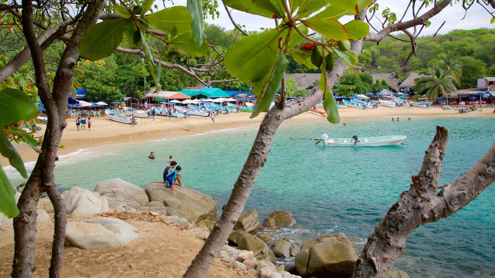 Playa Puerto Angelito que incluye una playa de arena, vistas generales de la costa y paseos en lancha