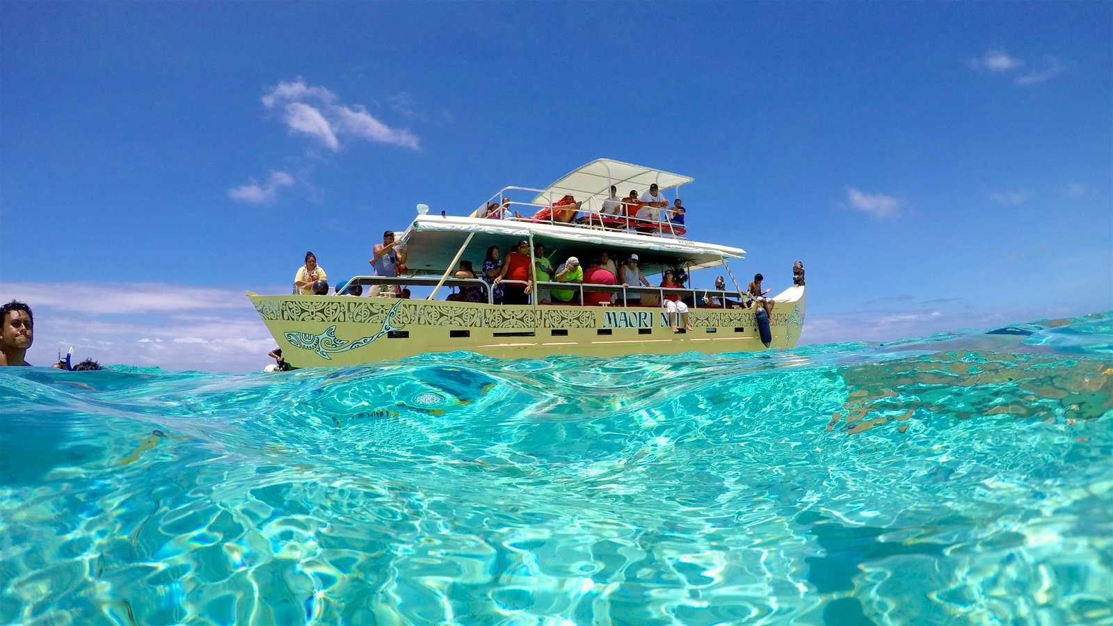 Bora Bora featuring boating and tropical scenes as well as a small group of people