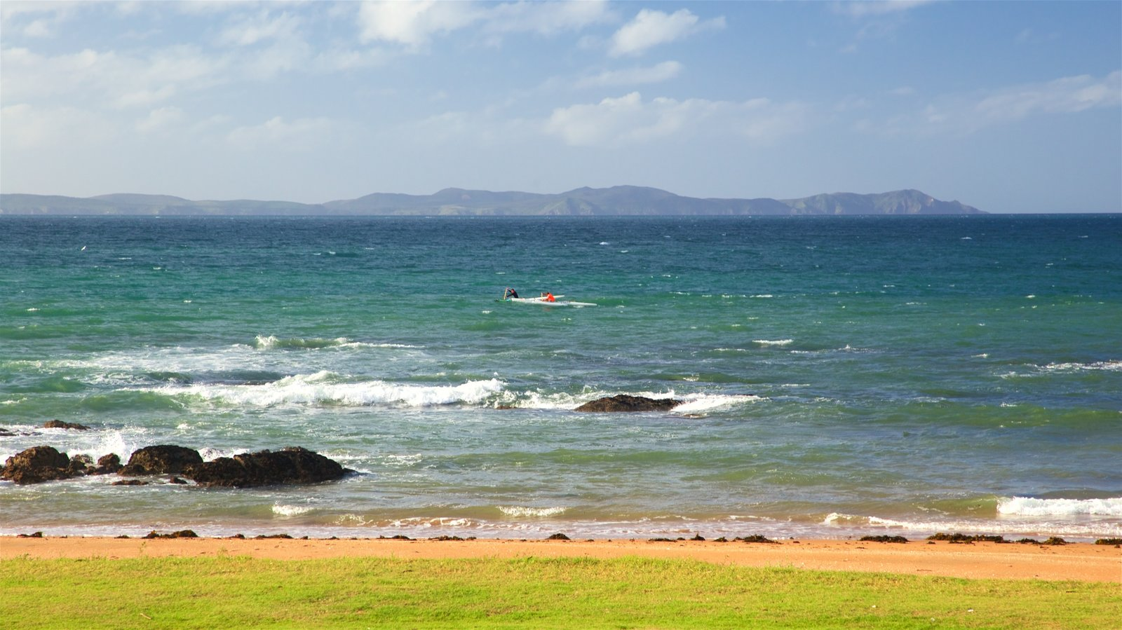 Cable Bay which includes a sandy beach, rugged coastline and general coastal views