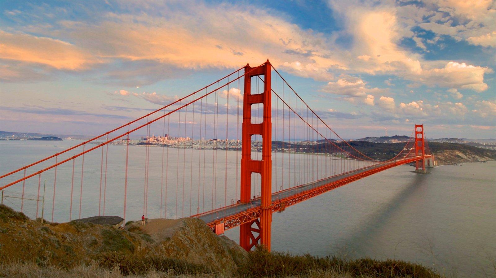 Golden Gate Bridge caracterizando uma ponte, um pôr do sol e um rio ou córrego