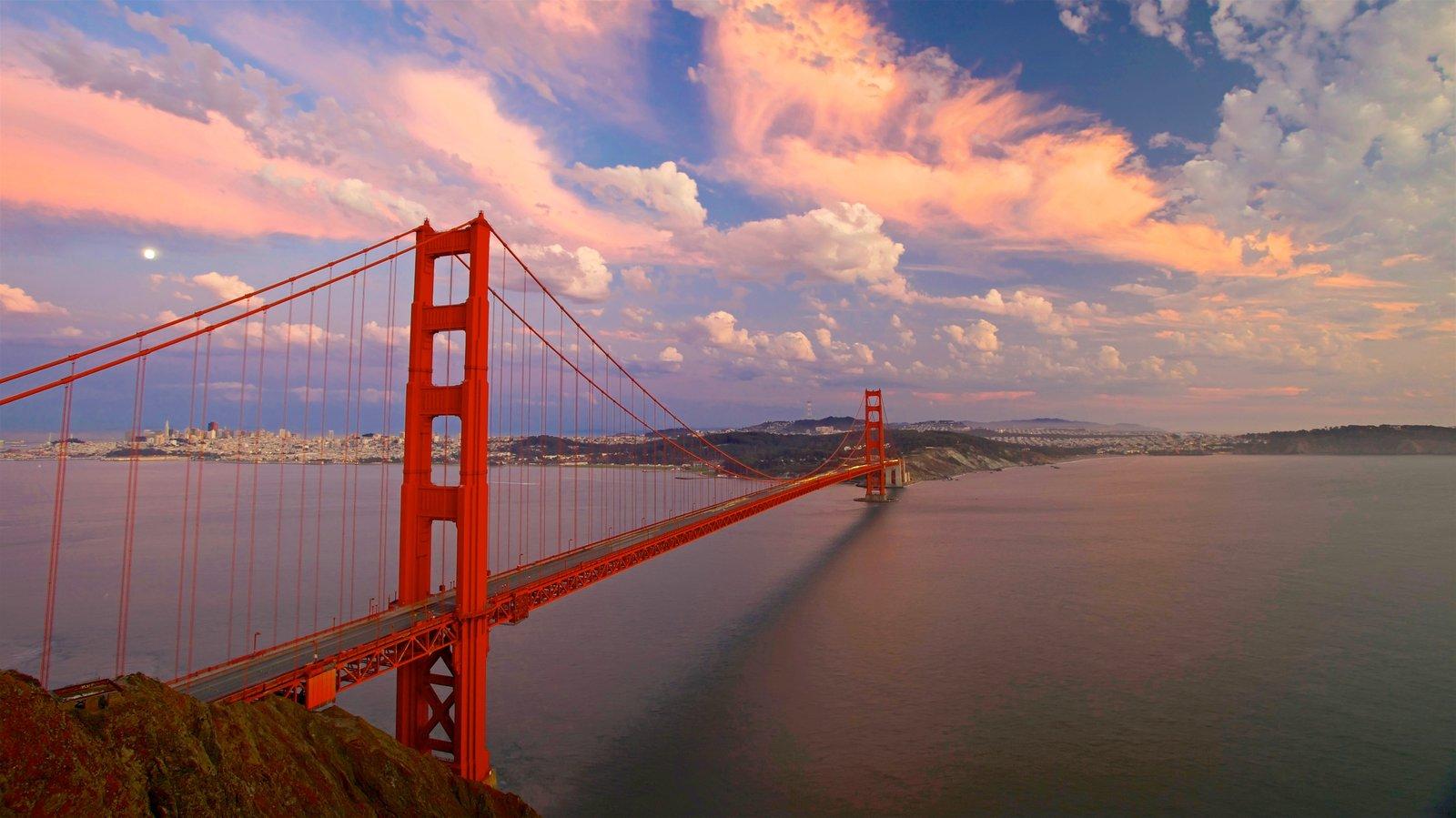 Golden Gate Bridge mostrando um pôr do sol, um rio ou córrego e uma ponte