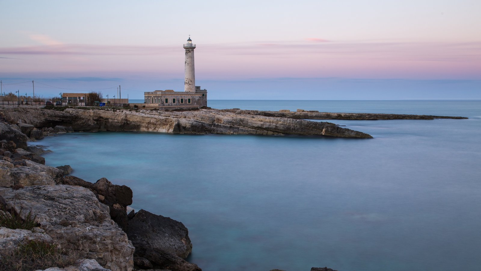 Augusta which includes a lighthouse, a sunset and rugged coastline