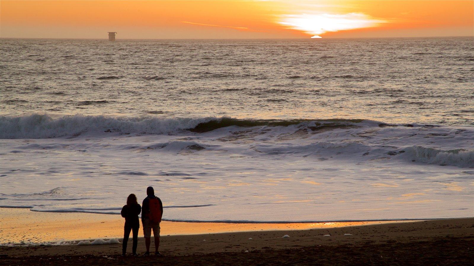 Baker Beach mostrando surfe, uma praia de areia e um pôr do sol