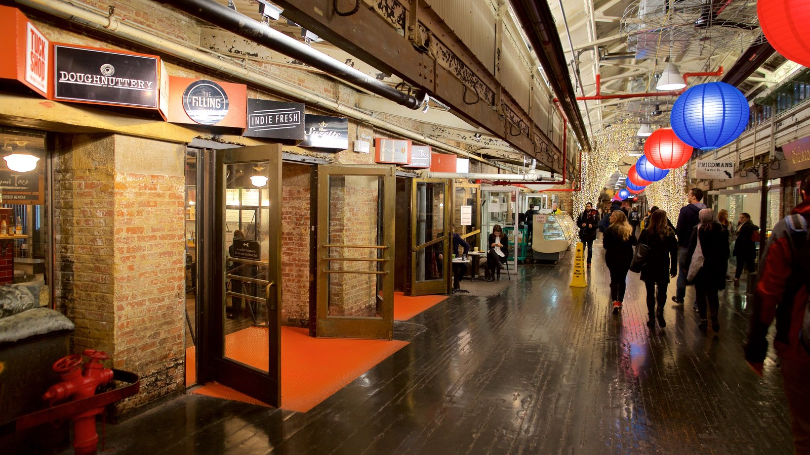 Chelsea Market featuring interior views as well as a small group of people