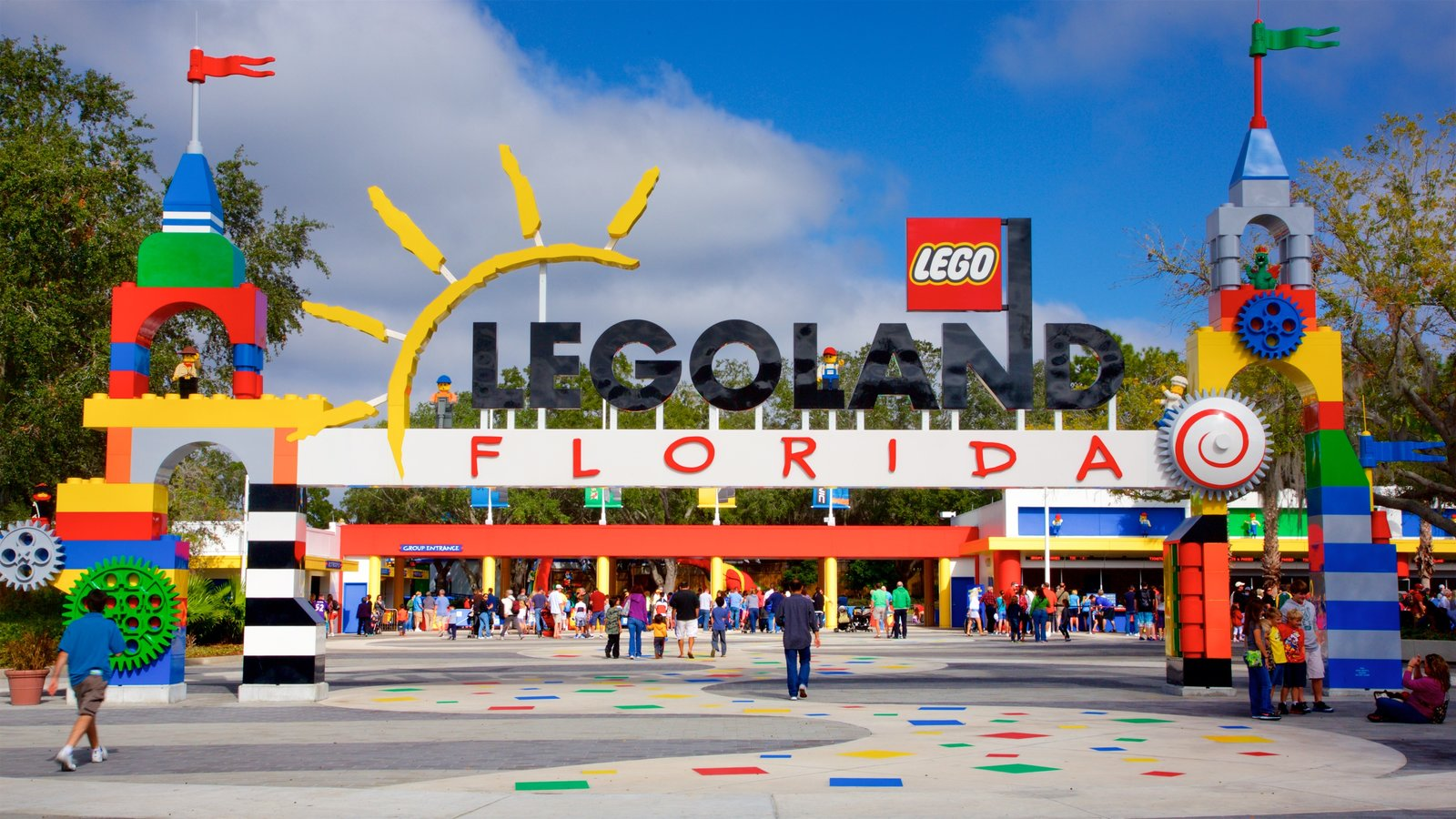 Legoland Florida showing signage and rides as well as a small group of people
