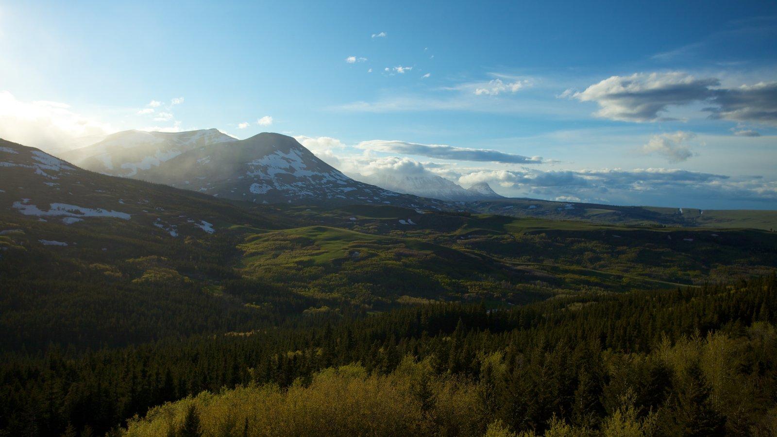 St. Mary Lake ofreciendo montañas, escenas tranquilas y una puesta de sol