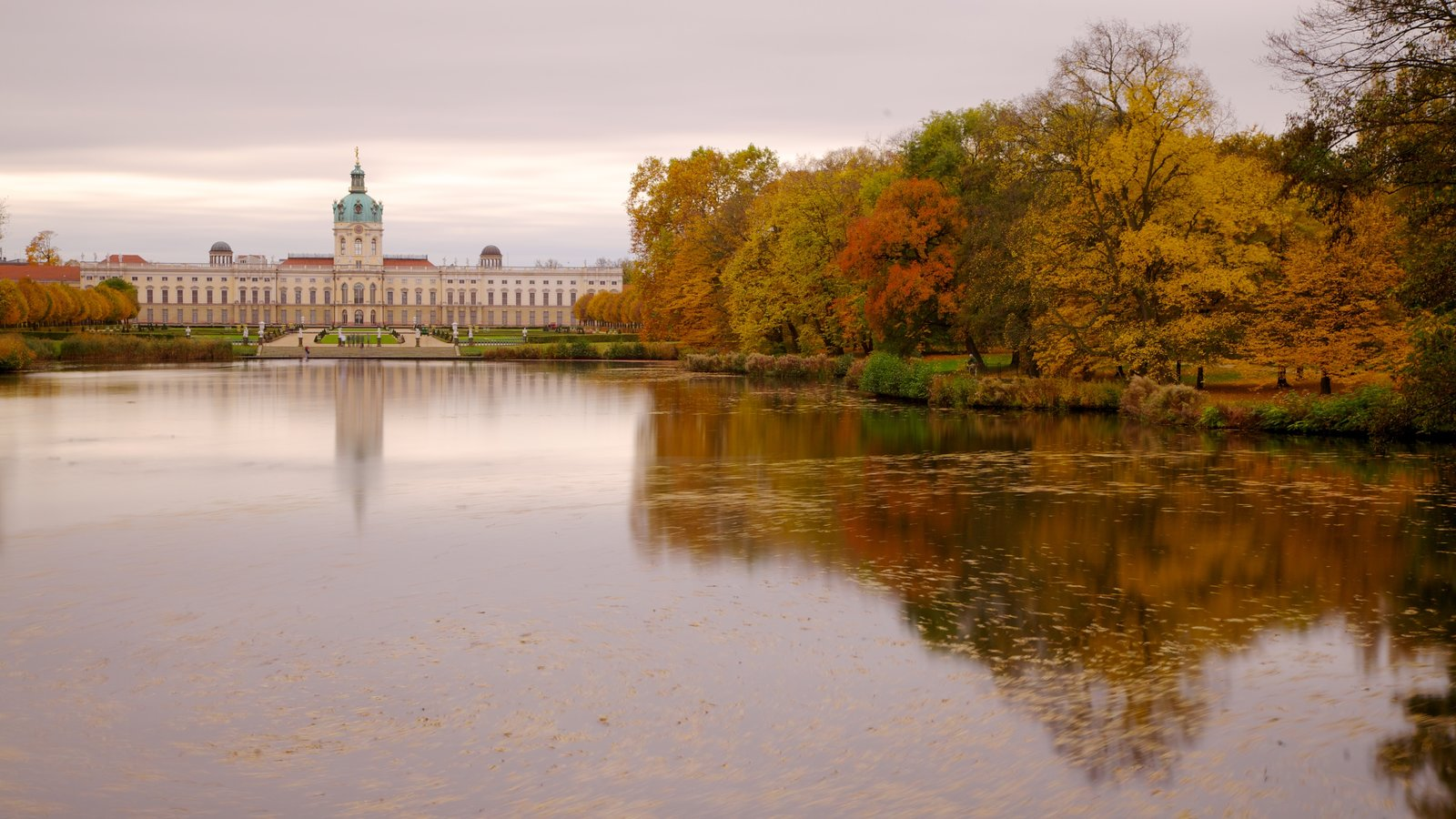 Schloss Charlottenburg featuring a sunset, a lake or waterhole and landscape views