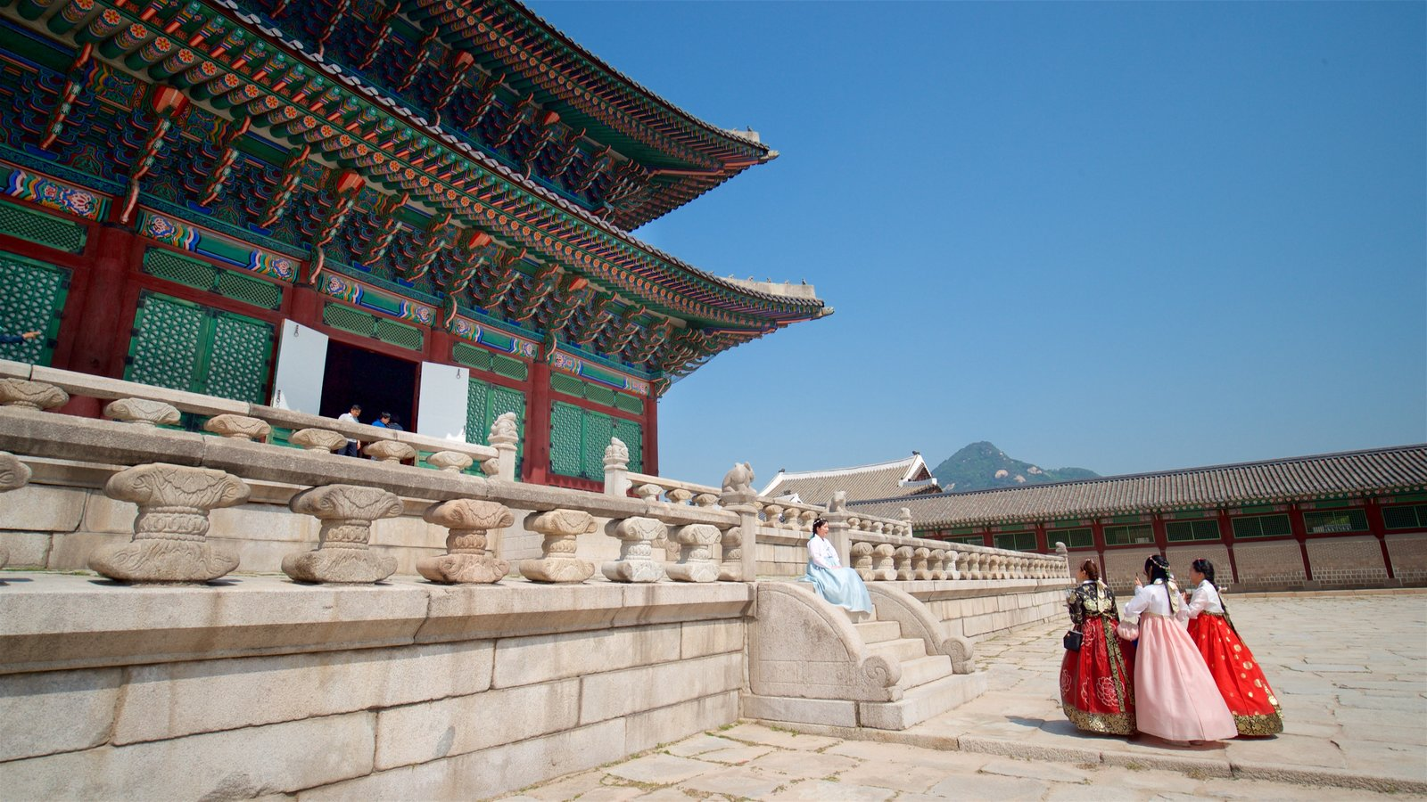 Gyeongbok Palace featuring a square or plaza and heritage elements as well as a small group of people