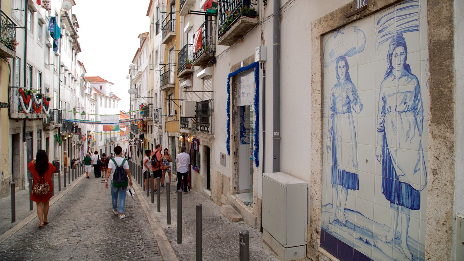 Alfama showing outdoor art and street scenes as well as a small group of people