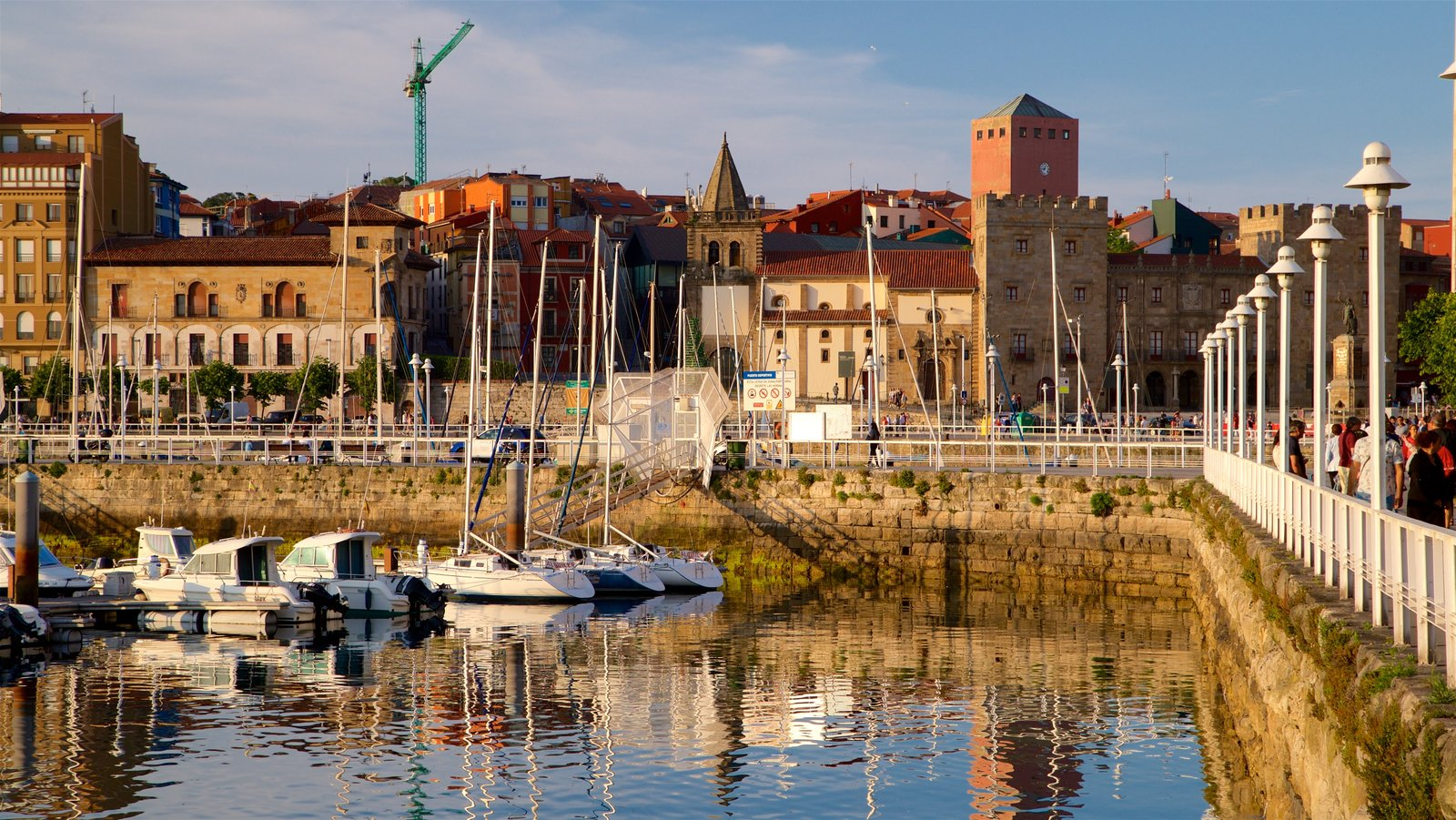 Gijon featuring a bay or harbor, a city and a sunset