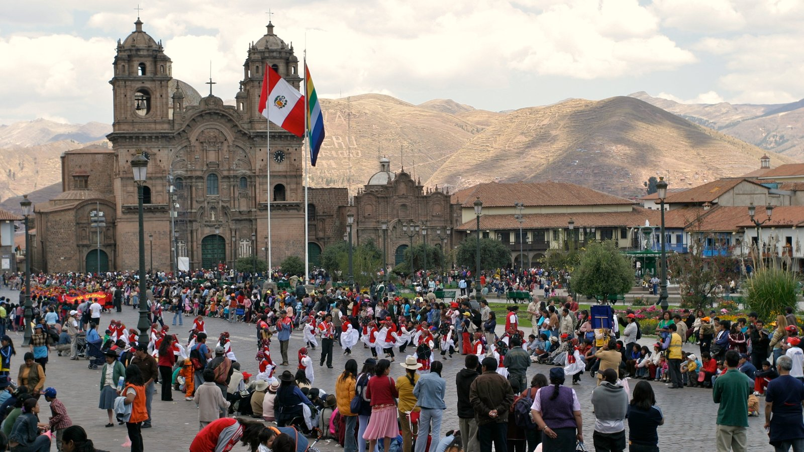 Cusco which includes a church or cathedral and heritage architecture as well as a large group of people