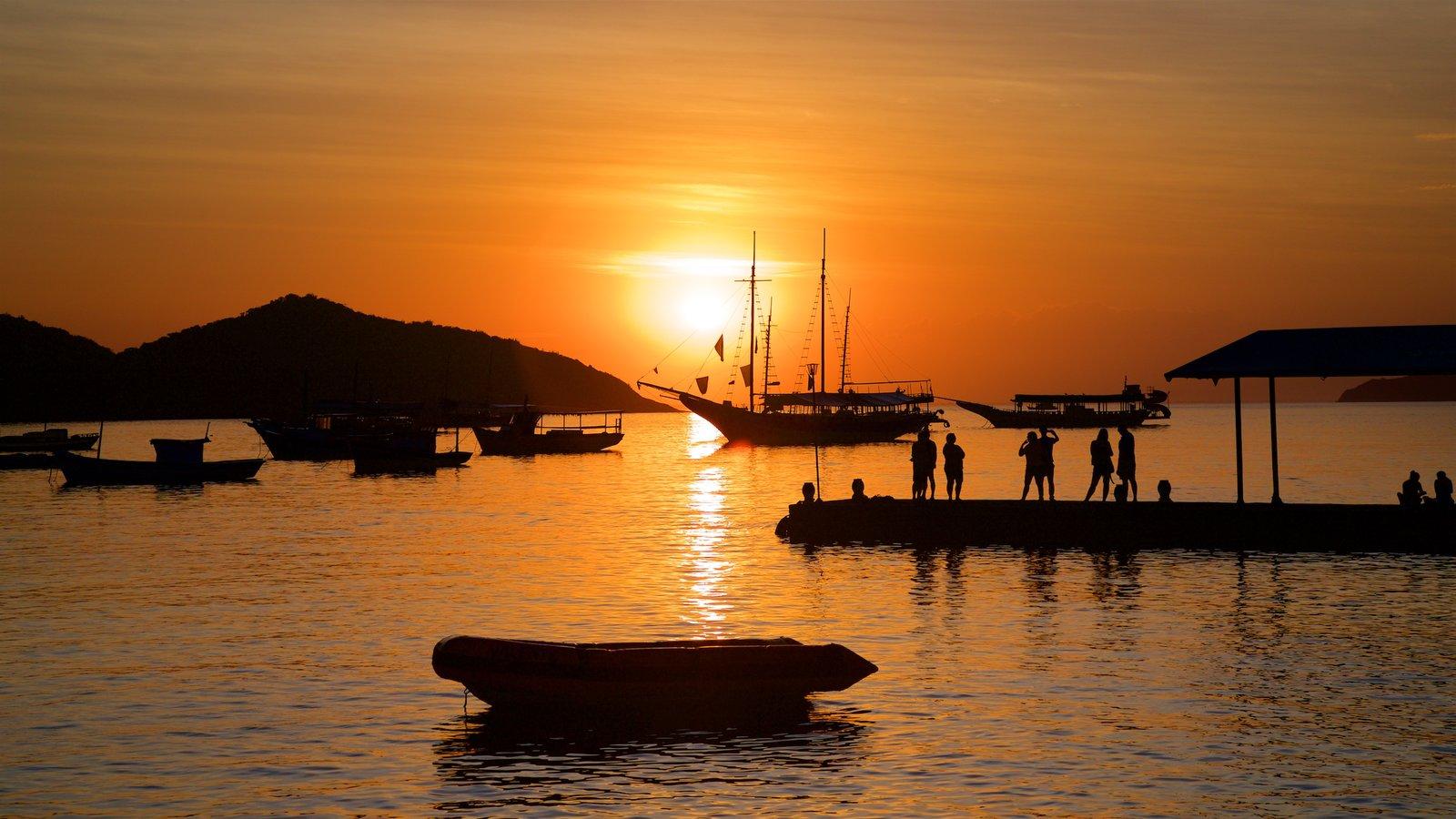 Búzios mostrando uma baía ou porto e um pôr do sol assim como um pequeno grupo de pessoas