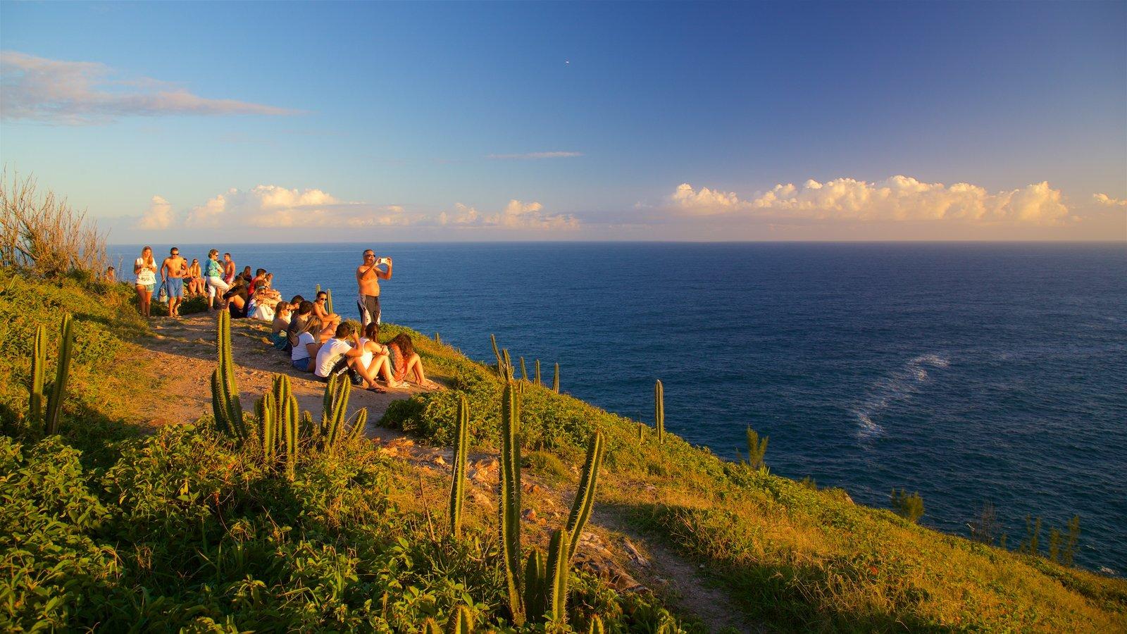 Mirante do Pontal do Atalaia caracterizando paisagens litorâneas e um pôr do sol assim como um pequeno grupo de pessoas