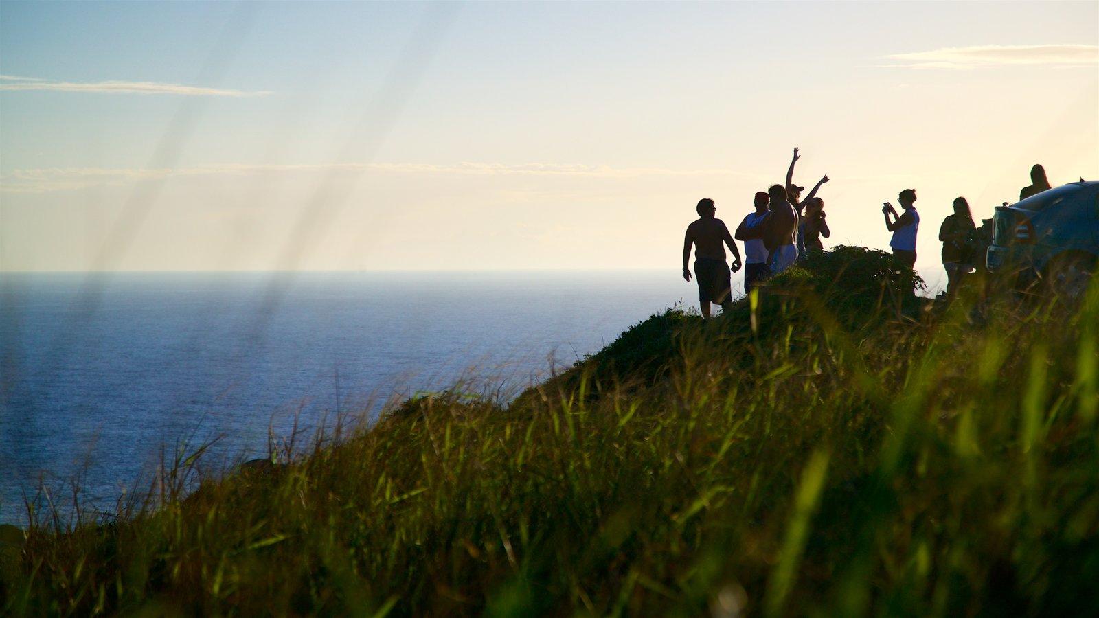 Mirante do Pontal do Atalaia mostrando paisagens litorâneas e um pôr do sol assim como um pequeno grupo de pessoas