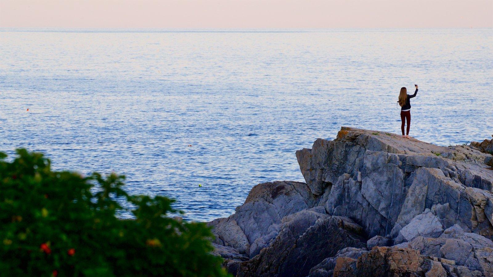 Parque Fort Williams ofreciendo vistas generales de la costa y costa rocosa y también una mujer