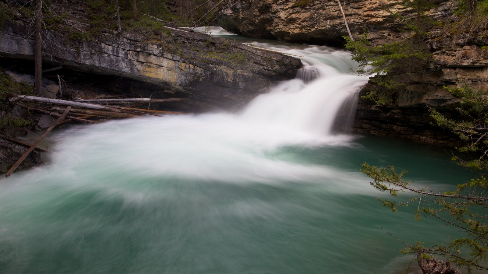 Johnston Canyon featuring landscape views, a waterfall and a gorge or canyon