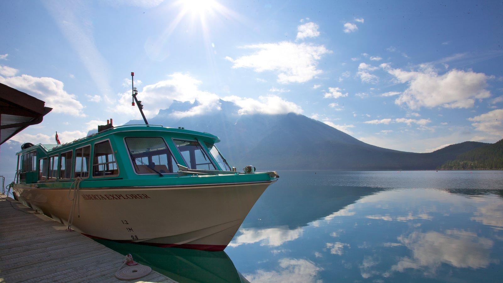 Lake Minnewanka showing a marina, mountains and boating