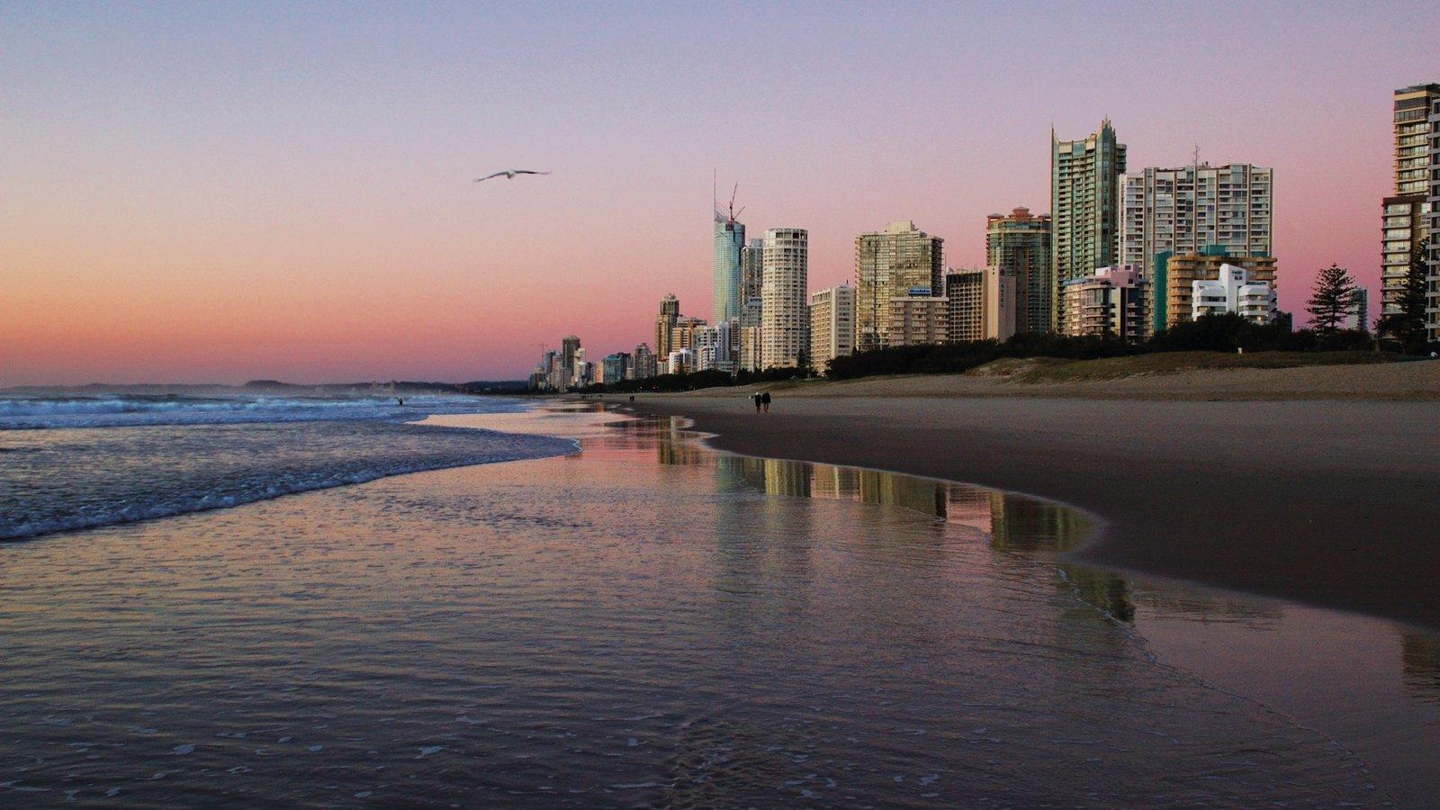 Gold Coast que incluye arquitectura moderna, una playa de arena y una puesta de sol