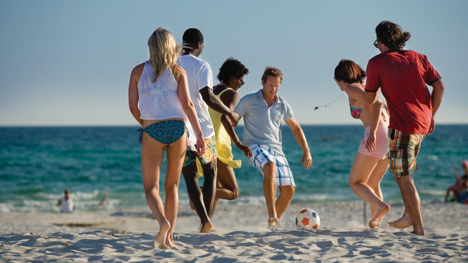 Panama City Beach que inclui uma praia de areia assim como um pequeno grupo de pessoas