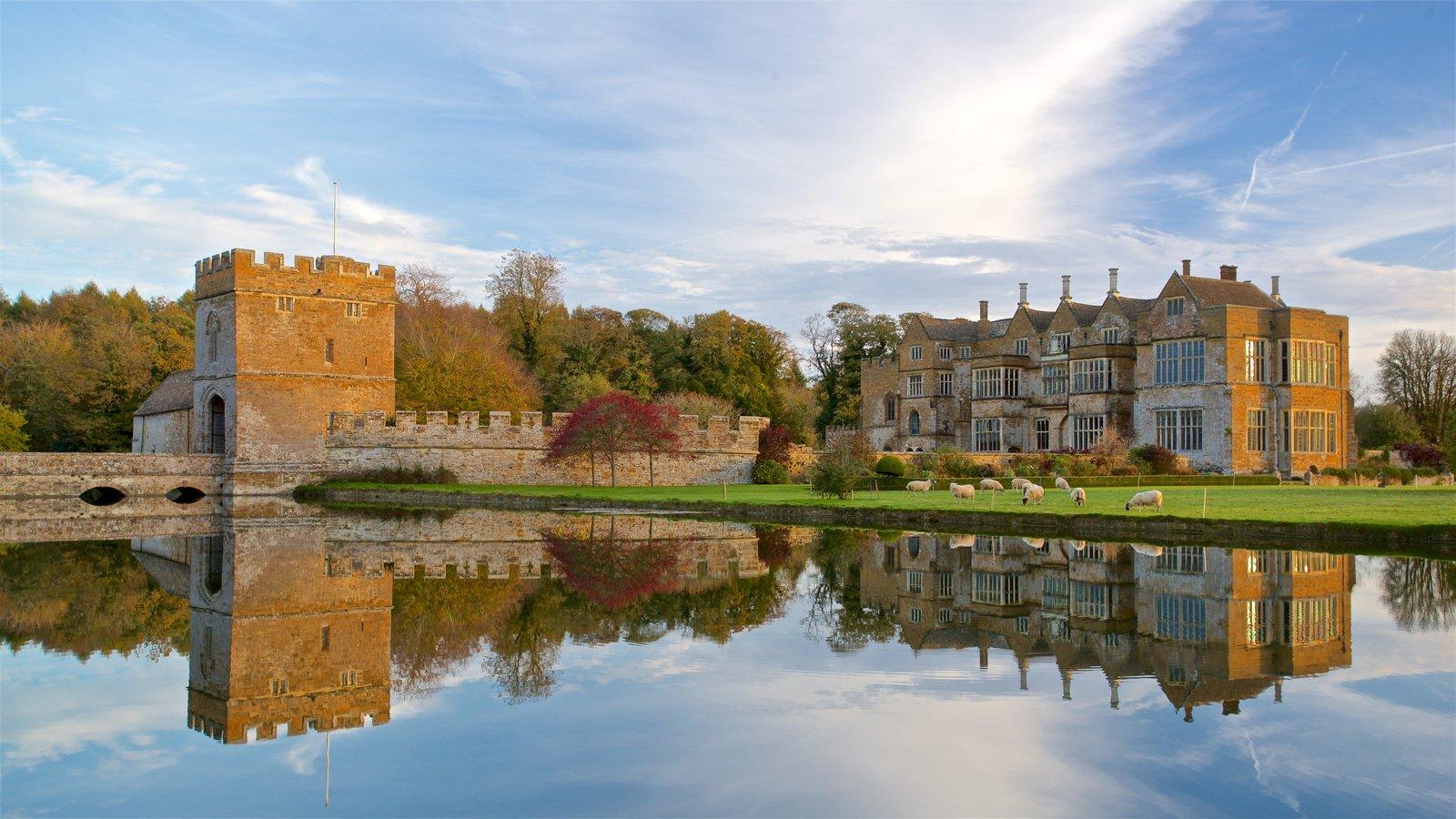 Broughton Castle que inclui um lago ou charco, arquitetura de patrimônio e um pequeno castelo ou palácio