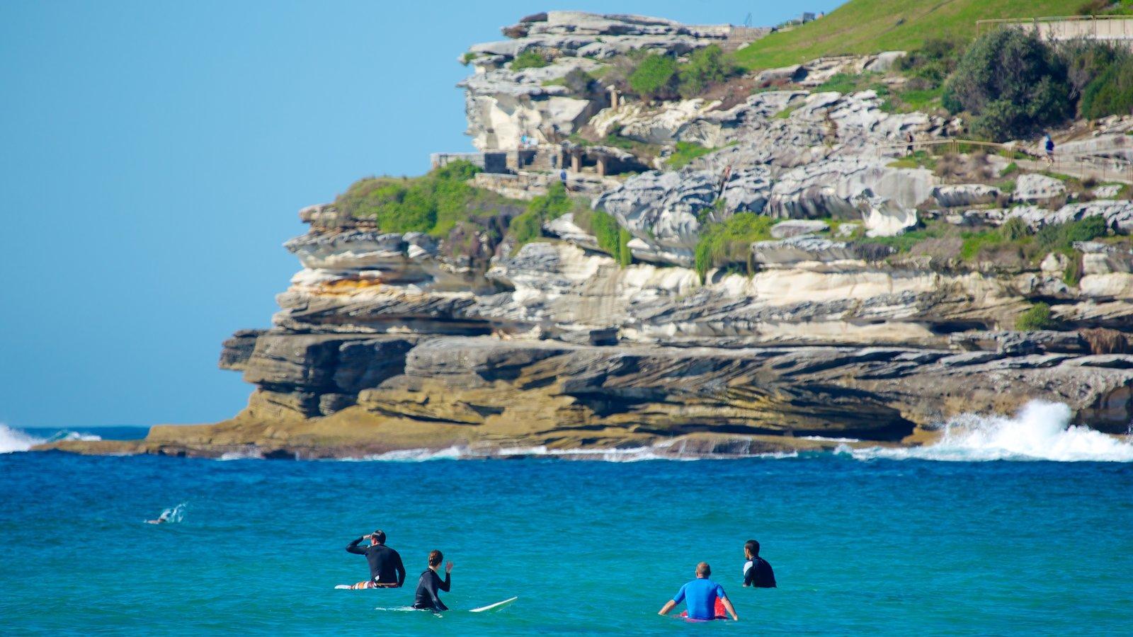 Bondi Beach showing rocky coastline, general coastal views and surfing