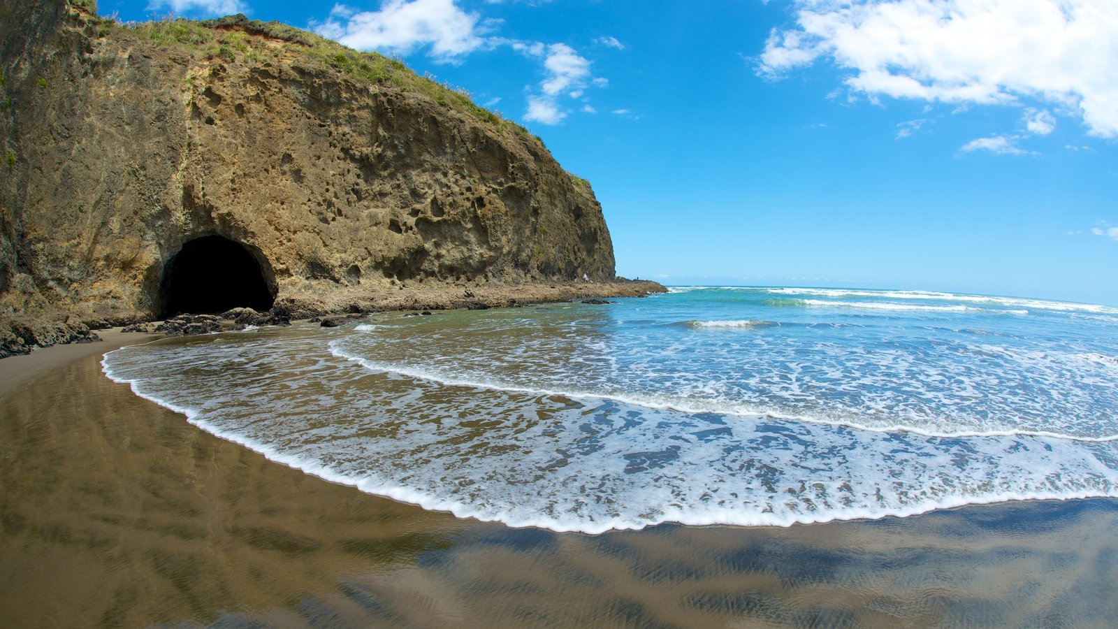 Bethells Beach featuring landscape views and rocky coastline
