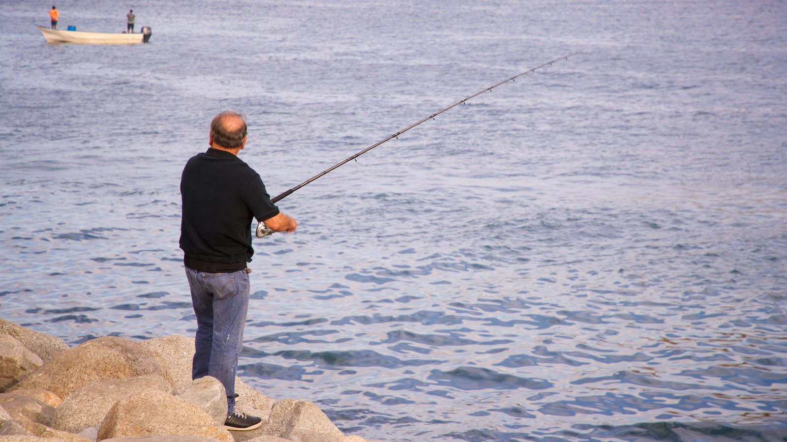 San Lucas Bay featuring fishing and general coastal views as well as an individual male
