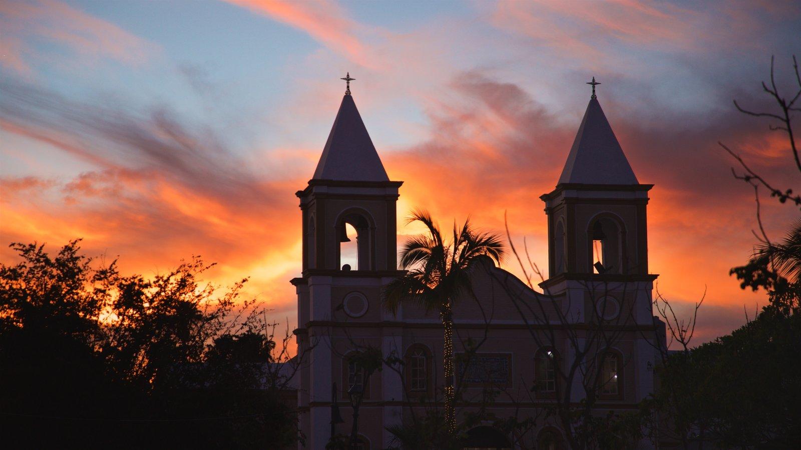 Missão de São José mostrando um pôr do sol e uma igreja ou catedral