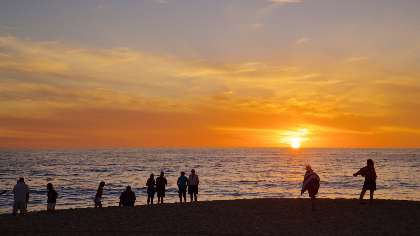 Todos Santos which includes general coastal views and a sunset as well as a small group of people
