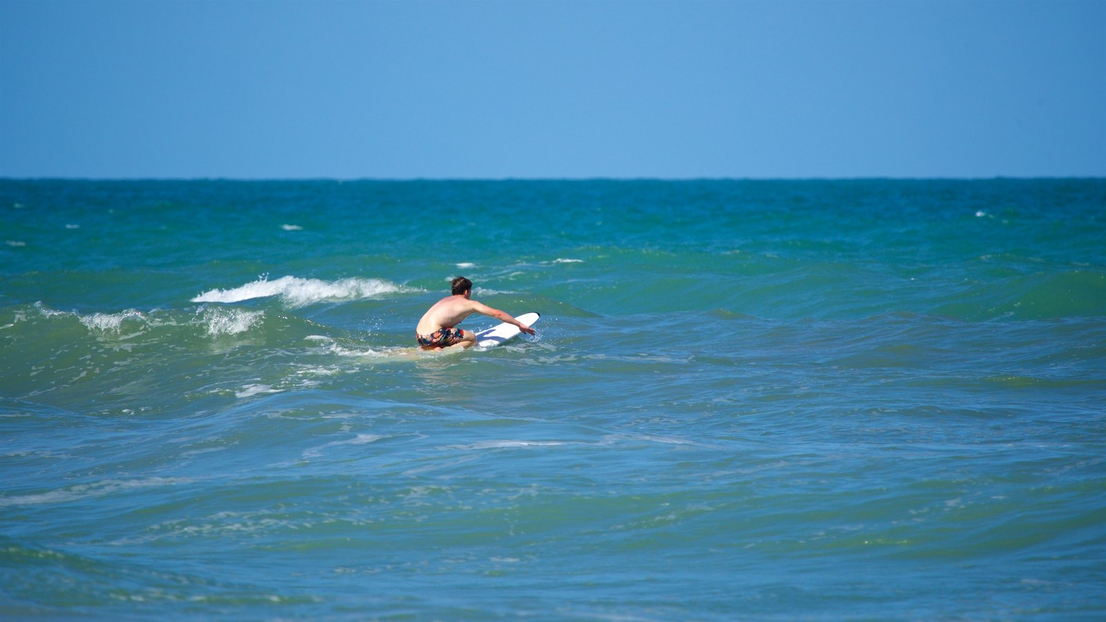 Cocoa Beach which includes general coastal views and surfing as well as an individual male