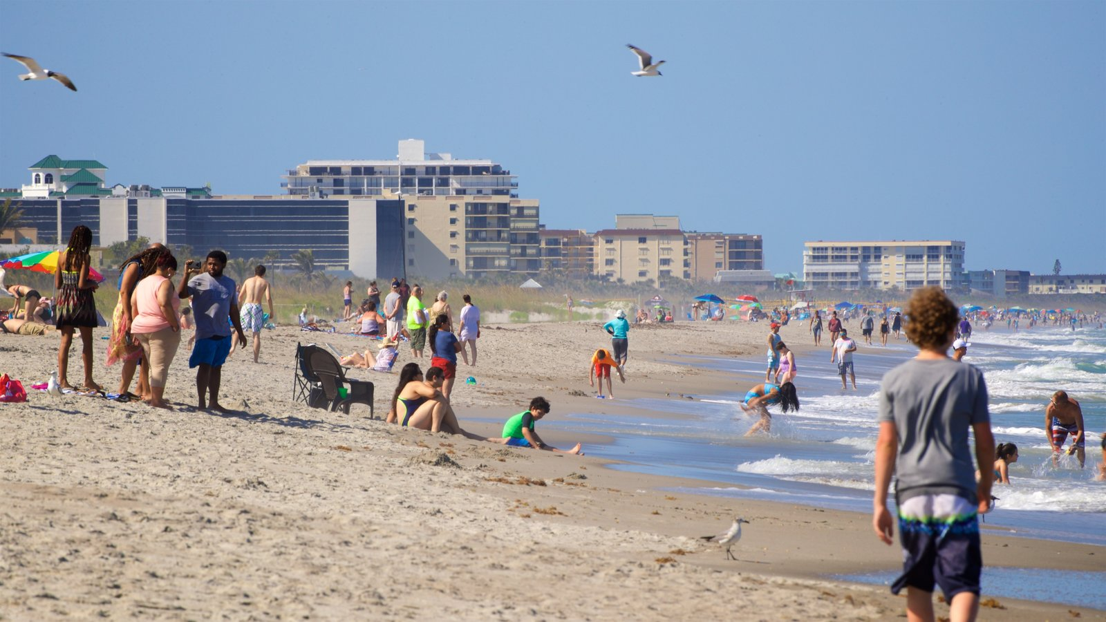 Cocoa Beach showing a beach and general coastal views as well as a small group of people